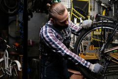 Handsome stylish male wearing a flannel shirt and jeans coverall, working with a bicycle wheel in a repair shop. A. A handsome stylish male wearing a flannel Royalty Free Stock Photo