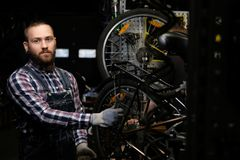 Handsome stylish male wearing a flannel shirt and jeans coverall, working with a bicycle wheel in a repair shop. A. A handsome stylish male wearing a flannel Royalty Free Stock Images