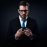 Handsome stylish man in elegant black suit using mobile phone. Royalty Free Stock Photo