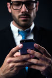 Handsome stylish man in elegant black suit using mobile phone. Royalty Free Stock Photography