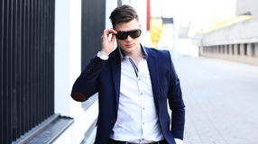 Handsome stylish man in elegant suit and sunglasses in the street. Royalty Free Stock Photos