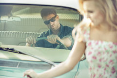 Handsome and stylish man giving young woman a lift Stock Photography