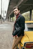 Handsome stylish man in leather jacket leaning at yellow car and looking. At camera stock image