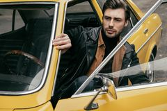 Handsome stylish man in leather jacket looking away while opening door of yellow. Vintage car royalty free stock photos