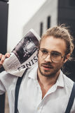 Handsome stylish man in spectacles holding newspaper and looking away Stock Image