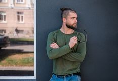 Handsome stylish man is standing near wall. stock image
