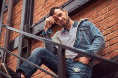 A handsome stylish man wearing a denim jacket posing on stairs outside, looking at a camera. royalty free stock photo