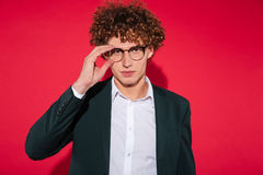 Handsome stylish man in white shirt and eyewear posing. And looking at camera isolated over red background Royalty Free Stock Photography
