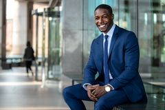 Handsome and stylish modern african american business man entrepreneur executive, sitting outside of office with cheerful smile