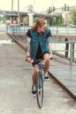 Handsome stylish tattooed man riding bicycle. On bridge stock photo