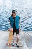 Handsome stylish tattooed man standing with skateboard on stairs. Near river stock photo