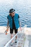 Handsome stylish tattooed man walking with skateboard on stairs. Near river stock photos