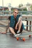 handsome stylish tattooed skater sitting on bridge royalty free stock photography
