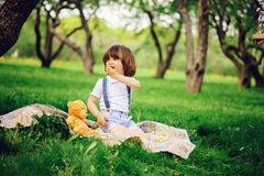 Handsome stylish 3 years old toddler child boy with funny face in suspenders enjoying sweets on picnic. In spring or summer garden or park Royalty Free Stock Photo