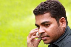 Handsome stylish young indian talking a cell phone. Photo of handsome young indian/south asian businessman talking and listening on cell phone with copy space Stock Photo