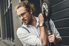 Handsome stylish young man in eyeglasses holding scooter stock photography