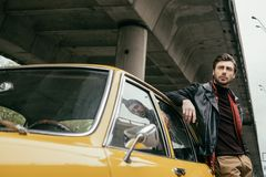Handsome stylish young man in leather jacket leaning at retro car. And looking away stock photo