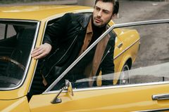 Handsome stylish young man in leather jacket opening door of yellow classic car. And looking away stock images