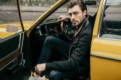 Handsome stylish young man in leather jacket sitting in vintage car and looking. At camera royalty free stock photos