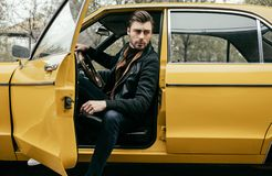 Handsome stylish young man in leather jacket sitting in yellow classic car. And looking away stock images