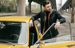Handsome stylish young man in leather jacket standing near retro car. And looking away stock photo
