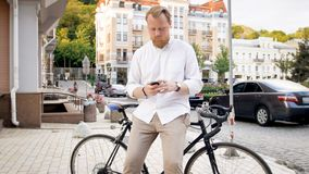 Handsome stylish man with smartphone leaning on vintage bicycle. Handsome stylish young man with smartphone leaning on vintage bicycle Stock Image