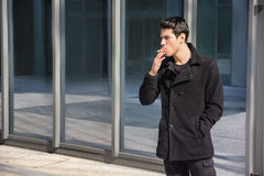 Handsome stylish young man smoking outside in Stock Photography