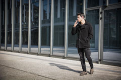 Handsome stylish young man smoking outside in Royalty Free Stock Images