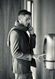 Handsome stylish young man using a pay phone Stock Photography