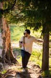 Handsome stylish young man wearing white t-shirt and sunglasses with backpack in his hand is traveling in the woods. Posing at camera near tree Royalty Free Stock Images