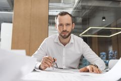 Handsome successful architect with compass working on building plans. At office royalty free stock photo