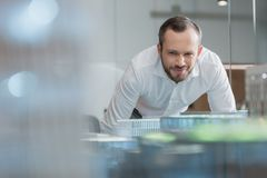 Handsome successful architect looking at building plans. At office royalty free stock photo