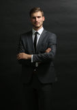 Handsome successful  business man  on black with arms cr Stock Image