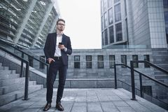 Business man stand at street holding a smartphone in office park royalty free stock photos