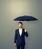 Handsome successful businessman with umbrella. Over grey background stock image