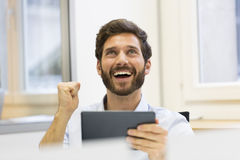 Handsome successful man using digital tablet Royalty Free Stock Photography