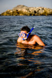 Handsome summer diving man with swimming mask. Young happy handsome summer diving man with swimming mask and snorkel preparing to dive in blue sea royalty free stock photo