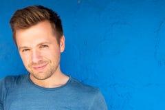 Handsome sunburnt man smiling against blue background royalty free stock photo