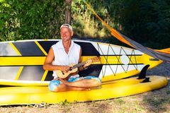 Handsome sup surfer relaxes in a river camping. Using sup board like sofa and plays ukulele Royalty Free Stock Photos