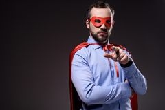 Handsome super businessman in mask and cape pointing on camera. Isolated on black stock photos