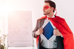 handsome super businessman in mask and cape showing blue shirt royalty free stock images