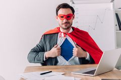 handsome super businessman in mask and cape showing blue shirt royalty free stock photos