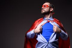 handsome super businessman in mask and cape showing blue shirt and looking away royalty free stock images