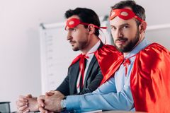 handsome super businessmen in masks and capes sitting at table stock photography