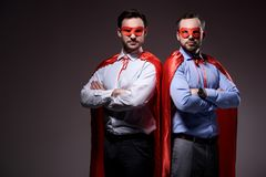 handsome super businessmen in masks and capes standing with crossed arms royalty free stock images
