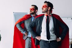 handsome super businessmen in masks and capes standing with hands akimbo stock photo