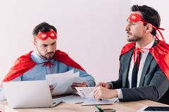 Handsome super businessmen in masks and capes working with documents. In office royalty free stock photography