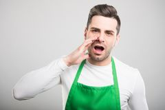 Handsome supermarket employer screaming out loud. On white background Royalty Free Stock Photo