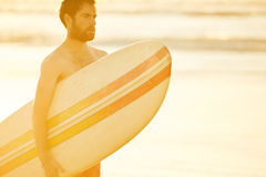 Handsome surfer holding a surfboard under his arm on beach. Caucasian male surfer holding a retro surfboard under his arm while looking sideways off camera, with Royalty Free Stock Images