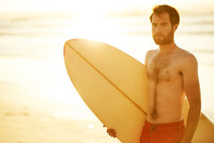 Handsome surfer holding a surfboard under his arm on beach. Caucasian male surfer holding a retro surfboard under his arm while looking sideways off camera, with Stock Image